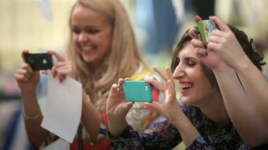 A group of girls laugh and make photo on their iphones — Stock Video