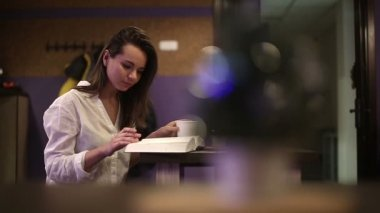 Girl student in a cafe reading a book. Slow motion — Stock Video