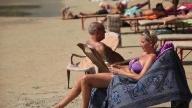 INDIA, GOA - DECEMBER - 2012: Tourists in India at Goa sunbathe on the beach near the sea — Stock Video