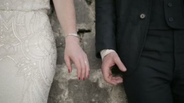 Adult man and woman hold hands on the stone wall background — Stock Video