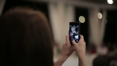 Girl photographs on the smartphone her boyfriend as he dances — Video Stock