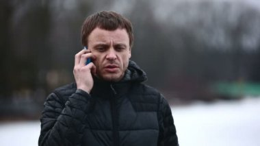 Adult serious man talking on the phone outdoors in winter — Stock Video