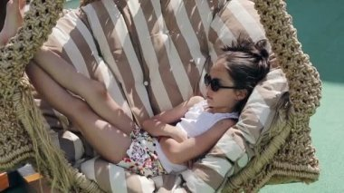 Female child relaxing outdoors in a hammock — Stock Video