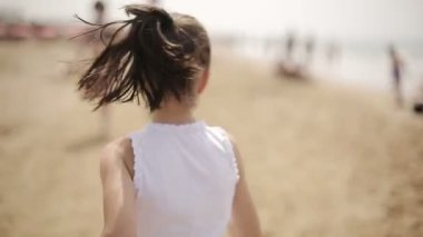 Happy child running along the beach and sometimes looks back — Stock Video