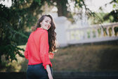 Beautiful girl in a red shirt posing on a street — Stock Photo