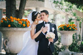 Beautiful bride and groom posing in a yard of a  castle — Stock Photo