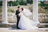 Bride and groom posing on the background of  ancient ruins — Stock Photo