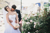 Happy and beautiful bride and groom kissing — Stock Photo