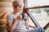 Woman sitting in a wicker chair on a balcony with a cup of tea — Stock Photo