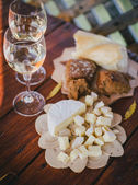 Two glasses of white wine with cheese and bread on a table — Stock Photo