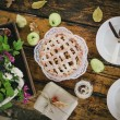 Homemade apple pie, apples and autumn leaves on the wooden table — Stock Photo #54246483