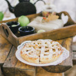 Homemade apple pie, apples and autumn leaves on the wooden table — Stock Photo #54246735