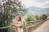 Pregnant woman with her husband on the mountains background — Stock Photo