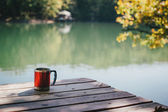 Red cup standing on a bridge near lake — Stock Photo