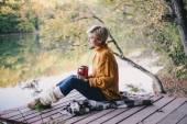 Blond with blue eyes sitting near lake with cup of hot tea — Stock Photo