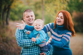 Happy family in blue stylish clothes walking in autumn forest — Stock Photo