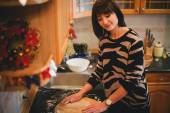 Young woman baking christmas cookies at the decorated kitchen — Stock Photo
