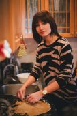 Young woman baking christmas cookies at the decorated kitchen — Foto Stock