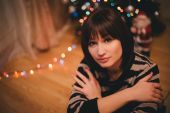 Pretty young woman near christmas tree in her cozy room — Stock Photo