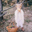 Little girl in a poncho eating yellow pear — Stock Photo #57174909