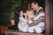 Happy family in a knitwear drinking tea in a forest — Stock Photo