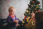 Mother and little son at home near Christmas tree — Stock Photo