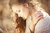 Young woman with beautiful curly hair posing in field at sunset — Stock Photo