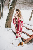 Young woman wrapped in blanket drinking hot tea in snowy forest — Stock Photo
