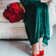 Beautiful woman with red lips sits on the couch with red roses — Stock Photo #63516511
