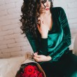 Beautiful woman with red lips sits on the couch with red roses — Stock Photo #63516587