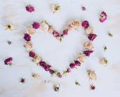 Dry rose flowers in heart shape on old wooden background — Stock Photo