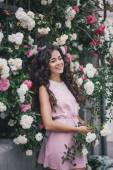 Beautiful young woman in a pink dress posing in a rose garden — Stock Photo