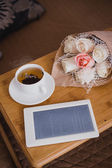 Wooden tray with tea, flowers and e-book standing on a bed — Stock Photo