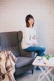 Mladá krásná těhotná žena sedící na židli šedá — Stock fotografie