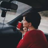 Pretty young woman drinking tea in a car with rainy weather outside — Stock Photo