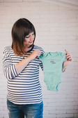 Young pregnant woman with her future baby's clothes — Stockfoto