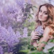 Young woman with long beautiful hair in a chiffon dress posing with lilac — Stock Photo #72498219
