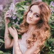 Young woman with long beautiful hair in a chiffon dress posing with lilac — Stock Photo #72498221