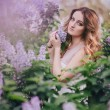 Young woman with long beautiful hair in a chiffon dress posing with lilac — Stock Photo #72498231