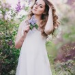 Young woman with long beautiful hair in a chiffon dress posing with lilac — Stock Photo #72498233