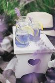 Homemade lavender lemonade with fresh lemons on a white wooden tray — Stock Photo