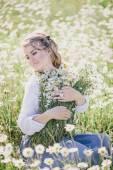 Young beautiful woman enjoying chamomile field among mountains — Stock Photo