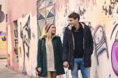 Happy couple walking by grafitti wall holding hands — Foto de Stock