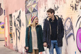 Happy couple walking by grafitti wall holding hands — Stock Photo