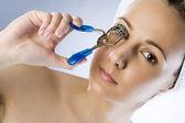 Cute woman with eyelash curler — Stock Photo