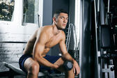 Muscular man training with dumbbells in gym — ストック写真