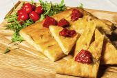 Cornbread on a wooden board with dried tomato and cherry tomatoe — Stock Photo