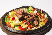 Vegetables and beef on iron hot plate — Stock Photo