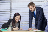 Businesswoman happily signing a document for business partner — Stock Photo