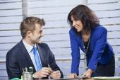 Man and woman in office smiling at each other — Stock Photo